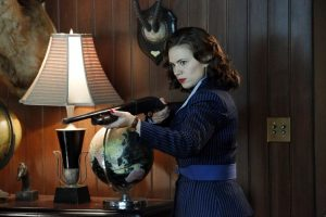 Actress Hayley Atwell as Peggy Carter in the show Agent Carter. She wears a blue and black striped suit, has bright red lipstick on, and is pointing a gun. She stands in a wood-paneled room with taxidermied antlers handing on the wall