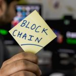 """A person holding a sticky note with the word """"BlockChain"""""""