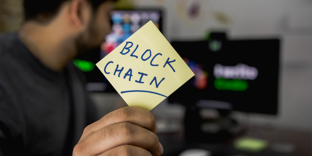 "A person holding a sticky note with the word ""BlockChain"""