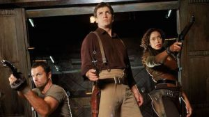 Photo of Jayne, Mal, and Zoe from Firefly. They each pointing guns straight ahead of them. They look serious and are wearing earthy colors