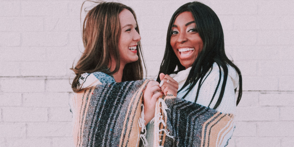 Two women wrapped in a beach blanket, laughing.