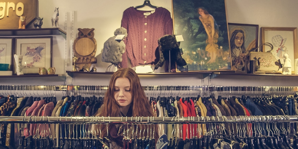 Image courtesy of Pexels usuer Burst [image description: a woman shopping in an aisle of clothes]