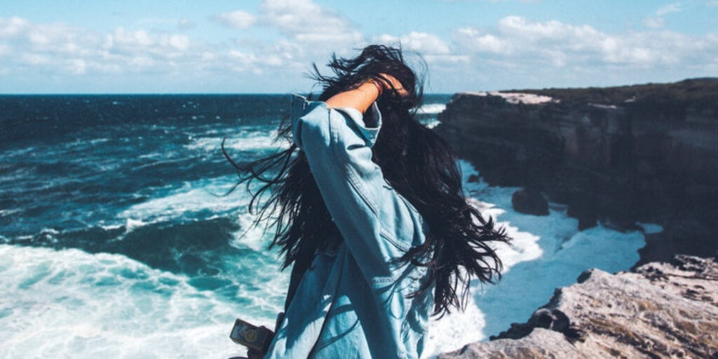 A photo of a girl with black hair looking at the ocean.