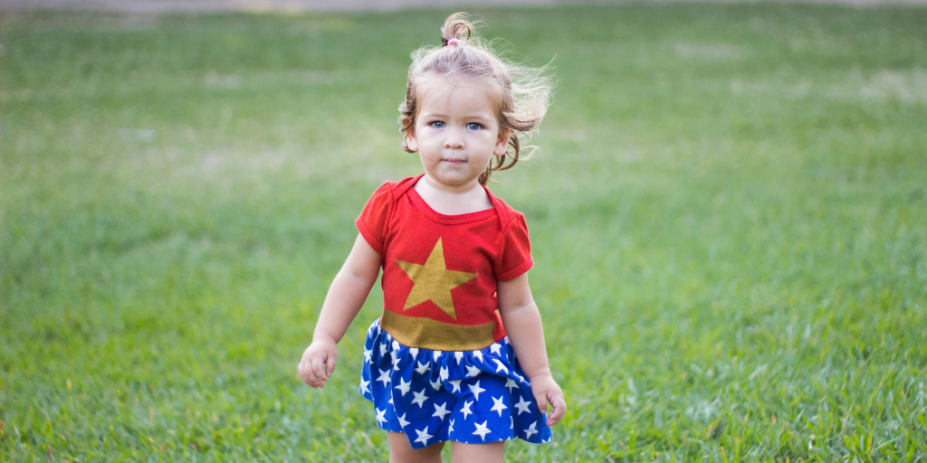 A young girl in a green field wearing a red shirt with a gold star and a blue skirt with white dots.
