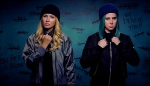 Actresses Eliza Bennett and Taylor Dearden as the characters Jules and Ophelia in the show Sweet/Vicious. Both wear wool hats, zipped up jackets, and have tough expressions on their faces. They stand in front of a wall with the names of boys crossed out and the text We Believe You