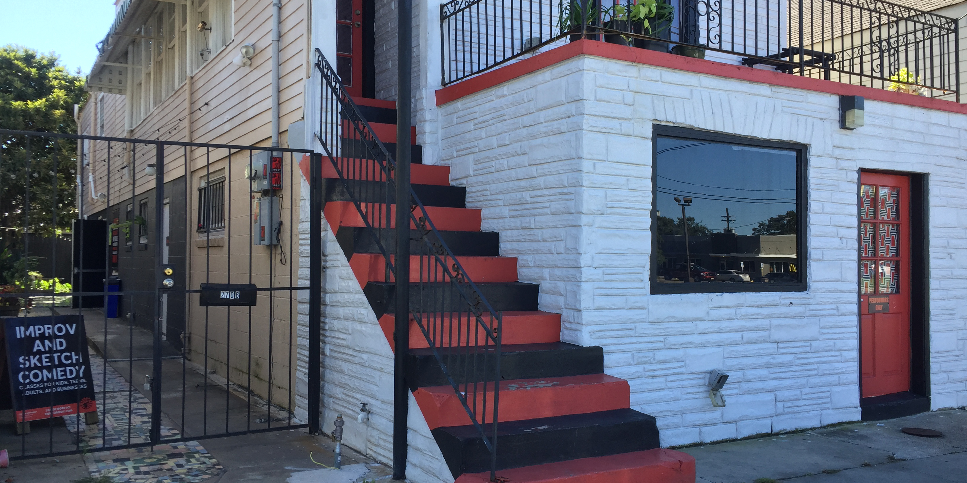 [image description: exterior of The New Movement theater. Building with bick front painted white, black and red alternating stairs and a gate to one side with a sign visible that says improv and sketch]
