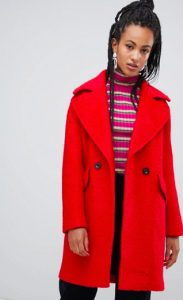 A woman faces the viewer with a serious expression on her face. She wears a red striped shirt and bright red coat