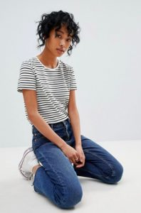 A woman models a striped shirt. She kneels on the ground with her hands in her lap