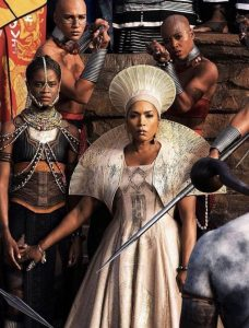 Queen Ramonda from Black Panther stares straight ahead defiantly, slightly holding back a young girl behind her. She wears an off-white gown with a matching Zulu-inspired hat