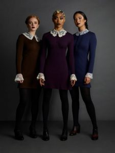 The Weird Sisters from The Chilling Adventures of Sabrina stand facing the viewer. They wear knee length dresses with lace sleeves and collars
