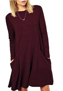 A photo from the chin down of a person with shoulder length blonde hair. They wear a long sleeve burgundy dress with pockets. They wear a silver necklace with a small pendant and stand leaning slightly to the left with their hands in the pockets