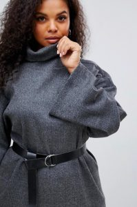 A person with long curly dark hair poses, staring at the viewer, holding her fist to her chin while grabbing the turtleneck of her grey sweater dress. She wears a black faux-leather belt around her waist
