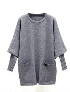 A long wool dress with wide bell sleeves and thinner wool sleeves underneath. There are two big pockets on the front