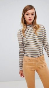 A person with long blonde hair wears a colorful striped turtleneck and tan jeans