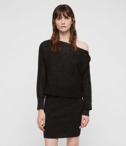 A woman wearing a black knit off the shoulder sweater looks straight ahead]
