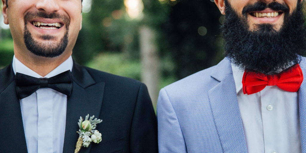 A photo of two men smiling, taken from the chin down. The man on the left has a close cropped goatee, wears a black suit jacket with a black bow-tie, and has a floral boutonniere. The man on the right has a mustache and thick beard. He wears a blue spotty jacket and a red bow tie