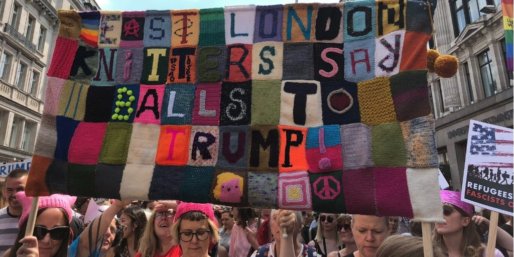 [Image Description: A group of protestors wear pussy hats or pink bandanas and carry a knitted blanket with words sewn into it that read East London Knitters Say Balls to Trump!] Photo by John Cameron on Unsplash