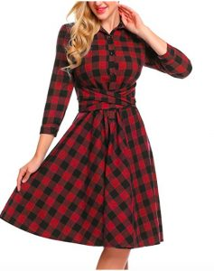 An image of someone from the nose down wearing a red and black plaid dress. The person is holding the skirt of the dress out and posing with their other hand resting on their neck