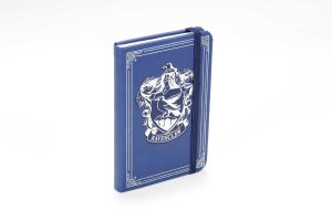 A blue notebook standing on one's end. It is closed with an elastic closure wrapped around it and is embossed in silver on the front. The cover features the Ravenclaw crest from the Harry Potter series, a raven sitting on a tree