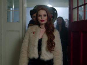 Cheryl Blossom from Riverdale walks through a set of doors. She has long red hair and wears a faux fur coat