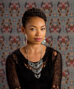 Sam White from Dear White People looks at the viewer, smiling slightly. She has braided hair coiled on her head and wears a big studded metal necklace, silver disk earrings, and a torn knit sweater