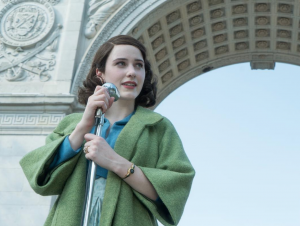 Miriam from The Marvelous Mrs. Maisel, a woman with short brown hair, wears a green coat with big sleeves. She stands in front of a microphone outside
