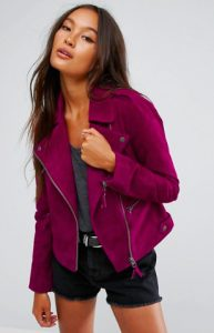 A woman wears a purple suede jacket