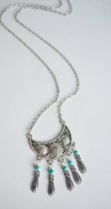 Image of a silver necklace from above featuring a crescent shape pendant and five attached charms with turquoise beads