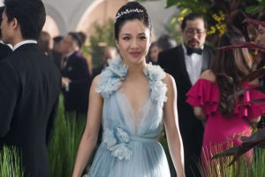 Rachel from Crazy Rich Asians passes through a crowd of people and is smiling widely. She wears a blue tulle dressed with flower embellishments on the shoulders and waist. Her hair is pulled into a bun and has a flower hairband in it
