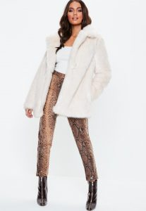 A woman wears a white faux fur coat