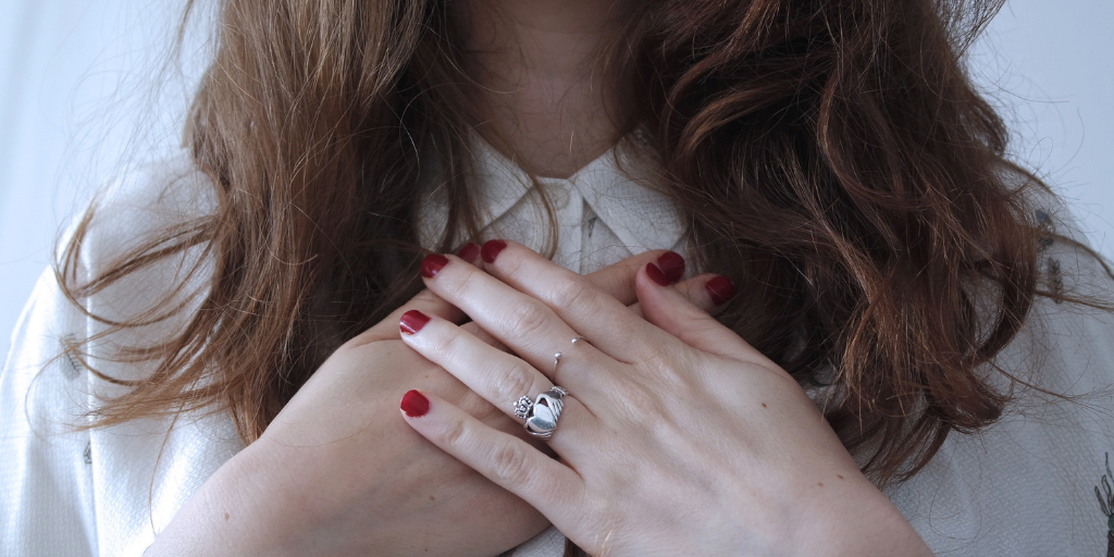 [Image Description: A woman with brown hair shown chin down with her hands crossed close to her chest, her left hand over her right hand. Her nails are painted red and on her third ring finger she is wearing a wedding ring.] Photo by Giulia Bertelli on Unsplash