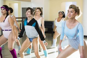 Female characters from the show GLOW wear 80s activewear and are exercising