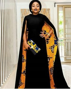 A person poses with their hand on their hip and wearing an all black dress with a cape that has yellow, blue, and silver African fabric on the inside. They wear a black purse that has matching fabric along the top