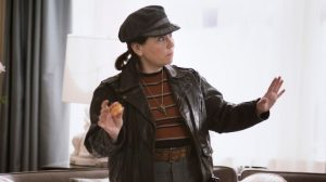 Susie Myerson, a character from The Marvelous Mrs. Maisel wears a newsboy cap, leather jacket, and striped shirt. She looks slightly concerned and holds her hands in front of defensively