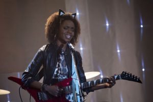 Josie McCoy from Riverdale stands up on stage playing guitar and singing with her eyes closed. She wears a leather jacket, leopard print dress and cat ears