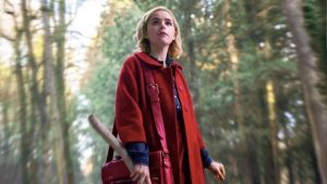 The character Sabrina from The Chilling Adventures of Sabrina looks at something curiously. She carries a stick and wears a bright red coat