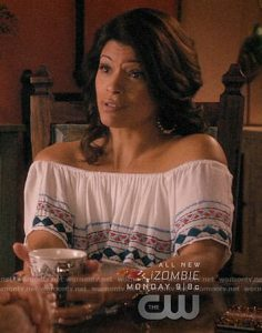Xiomara, a character from Jane the Virgin is in the middle of a conversation, holding a mug. She wears an off the shoulder embroidered top