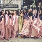 One bride wearing a green Pakistani dress stands with six bridesmaids on either side of her, the bridesmaids are all wearing pink skirts and different colored tops, they are all smiling and making funny faces, some have their hands in the air and they look happy.