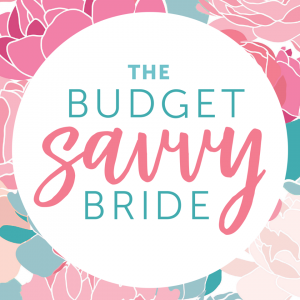 The logo for The Budget Savvy Bride written in teal and pink letters in a white circle, surrounded by pink flowers