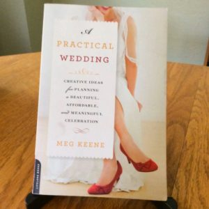 A photo of the book cover for A Practical Wedding, sitting up on a wooden table