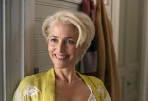 The character Jean from the show Sex Education, played by Gillian Anderson. She has short platinum blonde hair, blue-grey eyes, and wears a yellow robe over a white lacy nighty