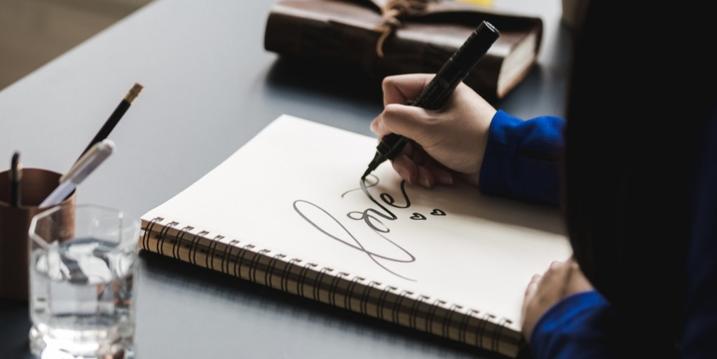 The word love with hearts written and drawn using a black marker in cursive on a blank coiled notebook by a woman in a blue sweater