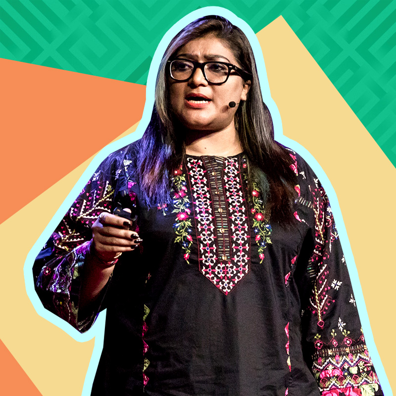 A photo of Nighat Dad giving a Ted Talk. She has long dark hair, wears glasses, and is wearing a black tunic with jewel-toned detailing. Via Instagram /@nighatdad