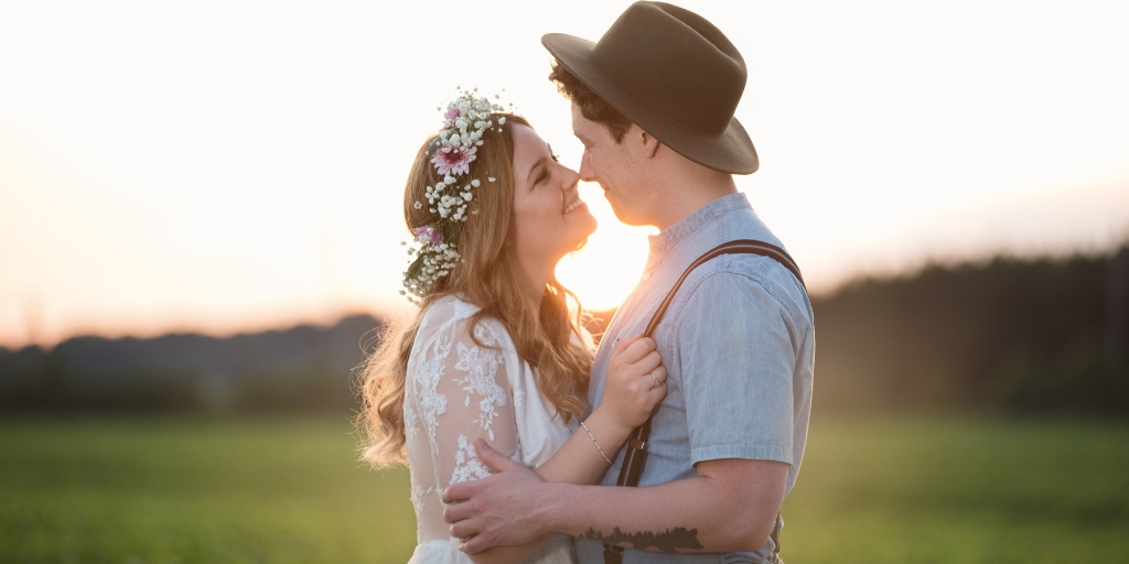 A married couple at sunset embracing and smiling at each other. The person on the left wears a flower crown and a white dress. The person on the right wears a wide brimmed hat, denim shirt, and suspenders