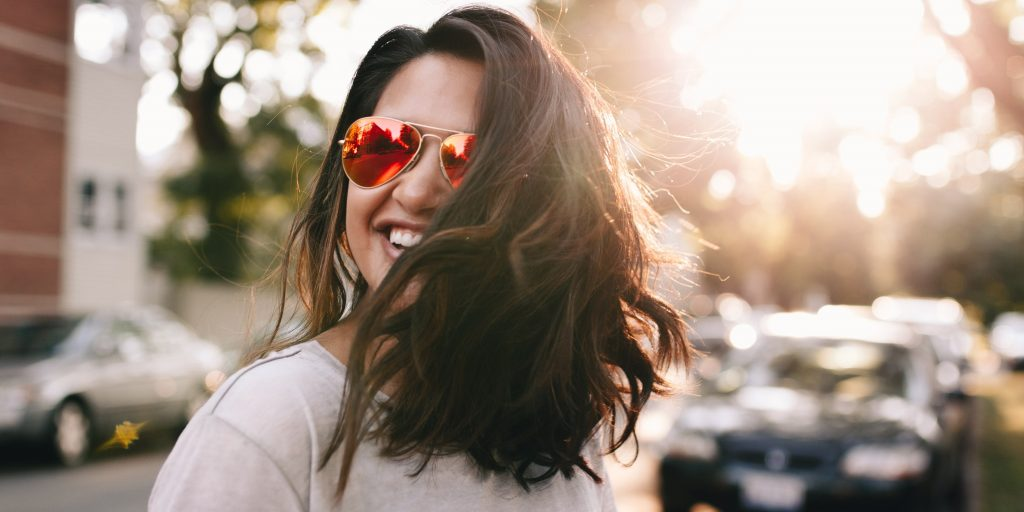 Woman in a white t-shirt and red sunglasses smiling in the sun.