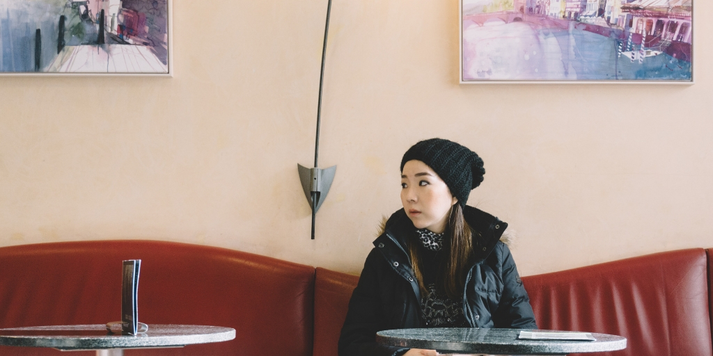 A woman with long dark brown hair, wearing a black wool hat and black winter jacket sits at a cafe on a red leather seat. She looks to the right with a slightly worried expression