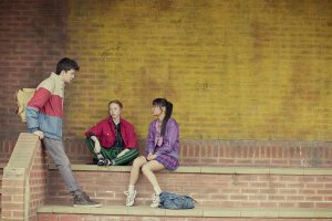 The character Otis from the show Sex Education stands, leaning against a brick wall, talking to two girls who are sitting on a ledge, listening to him. One of them looks skeptical and the other attentive