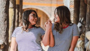 [Image Description: Two women with brown hair, wearing matching striped shirts hold hands and smile at each other.]