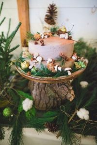A wedding cake decorated with brown icing, acorns, fake toadstools, and springs of evergreen