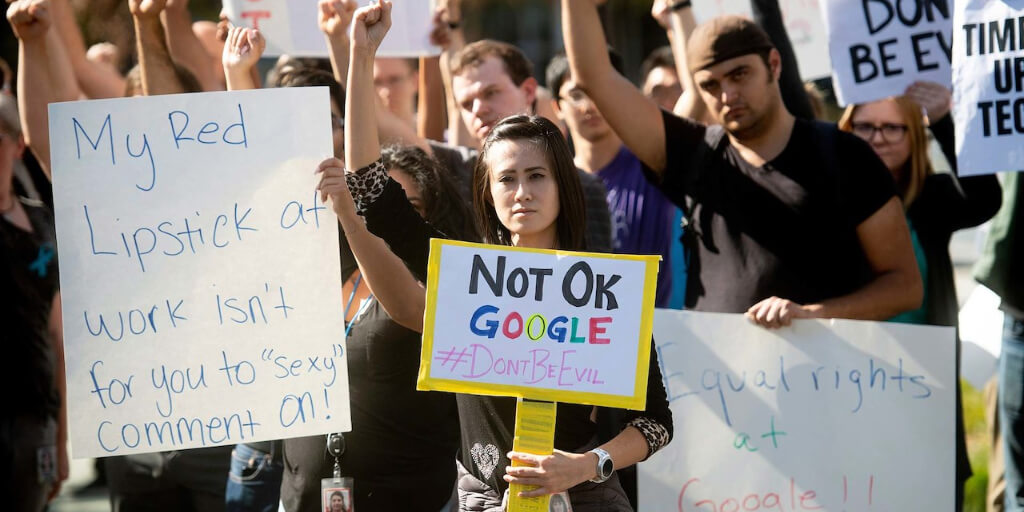 A group of workers from Google protesting outside, many of them holding signs.